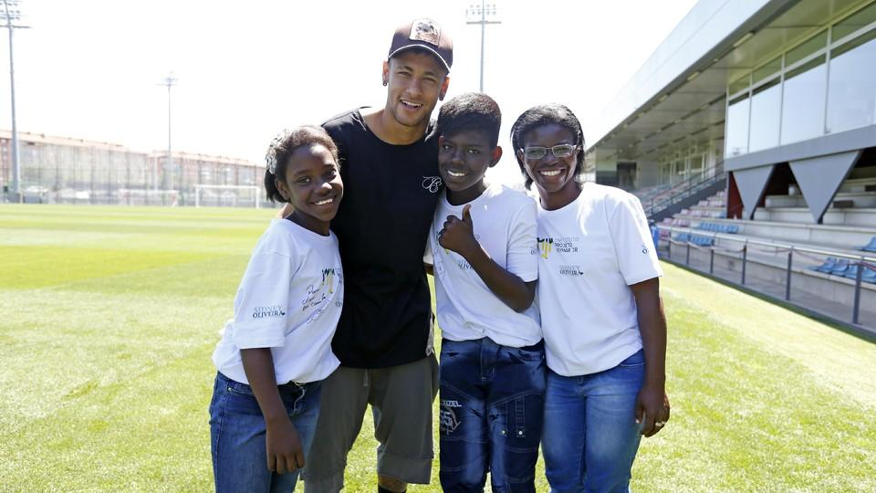 some children hug neymar at the instituto facilities